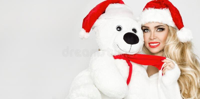 Piękny seksowny, uśmiechnięty blondynka model, ubierał w Święty Mikołaj kapeluszu, trzyma misia Piękno zmysłowa dziewczyna dla bo obraz royalty free