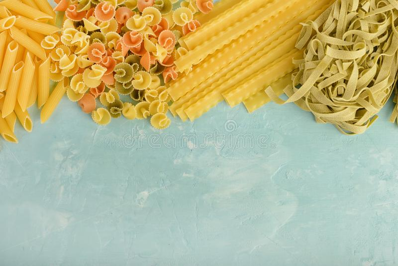 Piękny skład makaron z przestrzenią dla teksta Penne, Mafalde, Tagliatelle, spaghetti kłaść out na górze błękita obrazy stock