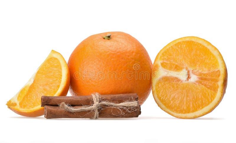 Piękny skład pomarańcze i doprawiający cynamonowi kije całe i pokrojone obrazy royalty free