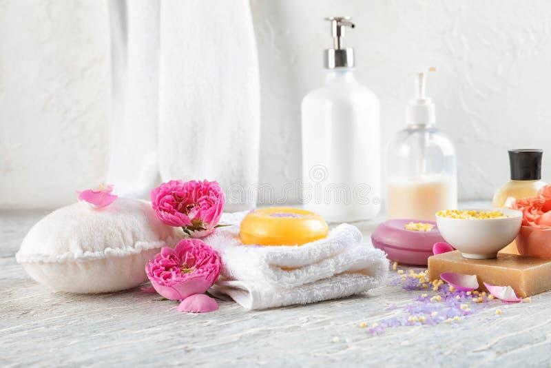 Piękny skład z kąpielowymi produktami i ręcznikami na światło stole zdjęcia stock