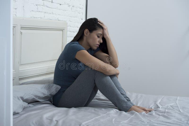 Piękny smutny i przygnębiony Łaciński kobiety obsiadanie na łóżku w domu udaremniał cierpienie depresję zdjęcia stock