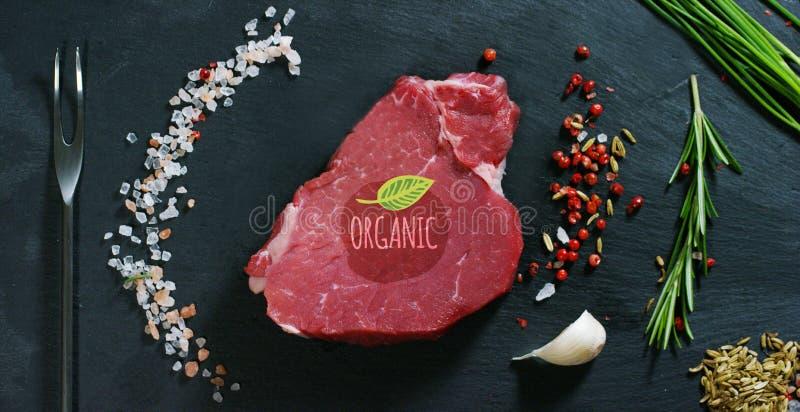 Piękny soczysty świeżego mięsa stek na stole z solą, rozmarynami, czosnkiem i pomidorem na czarnym tle, odgórny widok Pojęcie: fr zdjęcie royalty free