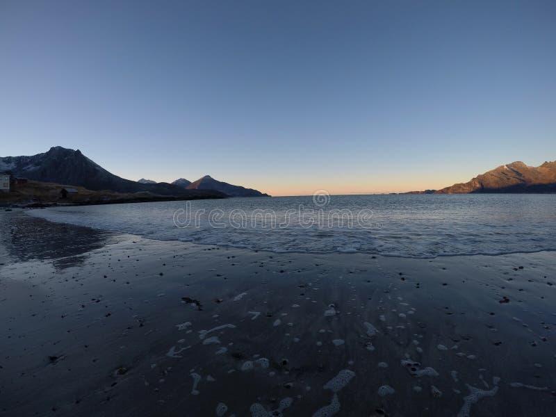Piękny spokojny błękit macha uderzający białą marznącą piaskowatą plażę w opóźnionej jesieni w arktycznym okręgu z głęboką górą i zdjęcia stock