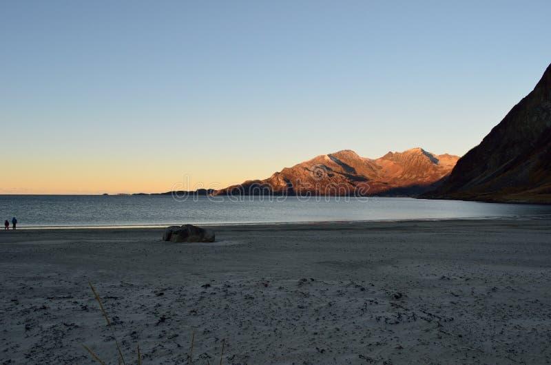 Piękny spokojny błękit macha uderzający białą marznącą piaskowatą plażę w opóźnionej jesieni w arktycznym okręgu z głęboką górą i zdjęcie stock