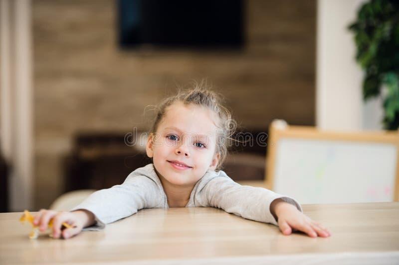Piękny spokojny małej dziewczynki obsiadanie przy drewnianym stołem fotografia stock
