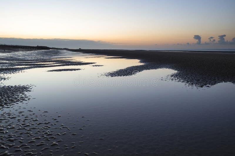 Piękny spokojny wschód słońca nad niskiego przypływu plażą zdjęcie stock