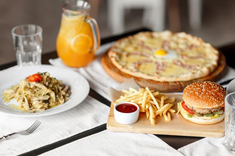 Piękny stół włoski makaron, pizza, hamburger i napoje, Selekcyjna miękka ostrość fotografia stock