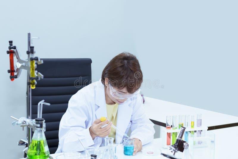 Piękny starszy żeński naukowiec miesza substancje w próbnej tubce obrazy stock