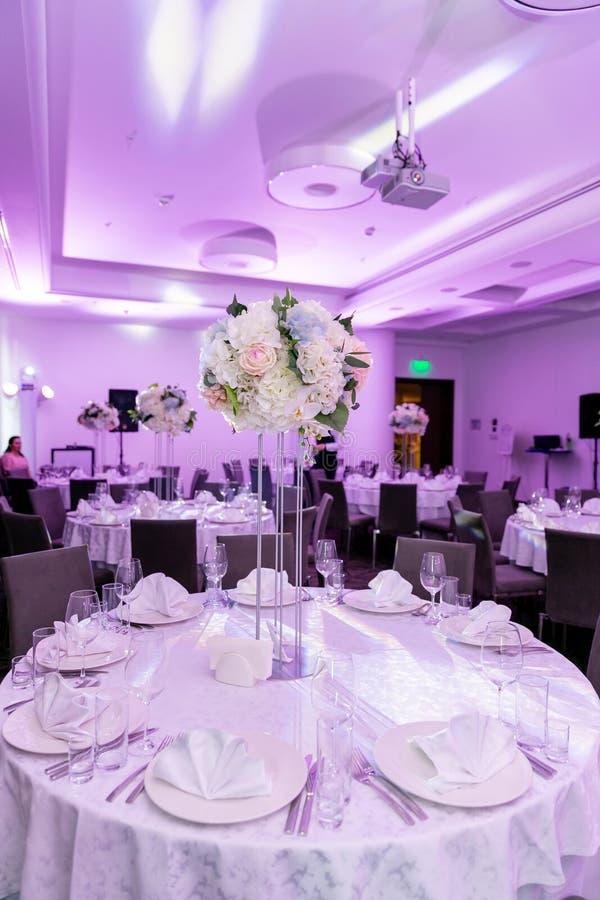 Piękny stołowy położenie z crockery i białego kwiatu przygotowania w wazie na wysokim trzonie dla przyjęcia, wesele lub fotografia stock