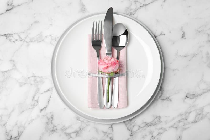 Piękny stołowy położenie z cutlery, pieluchą i talerzami na marmurowym tle, zdjęcia stock