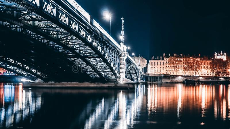Piękny strzał długi stal most nad rzeką z światłami i odbiciami w rzece przy nocą fotografia royalty free