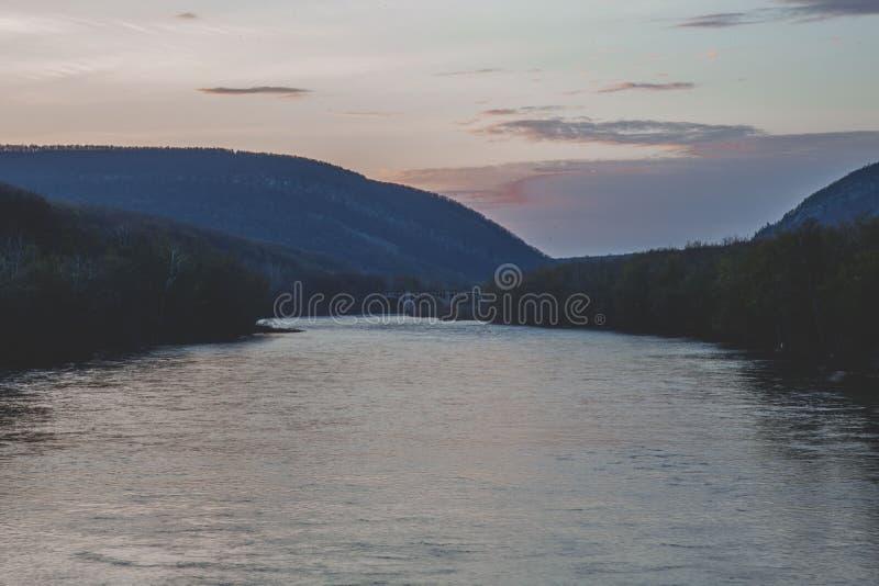 Piękny strzał rzeka otaczająca drzewami pod różowawym niebem podczas złotej godziny obraz royalty free