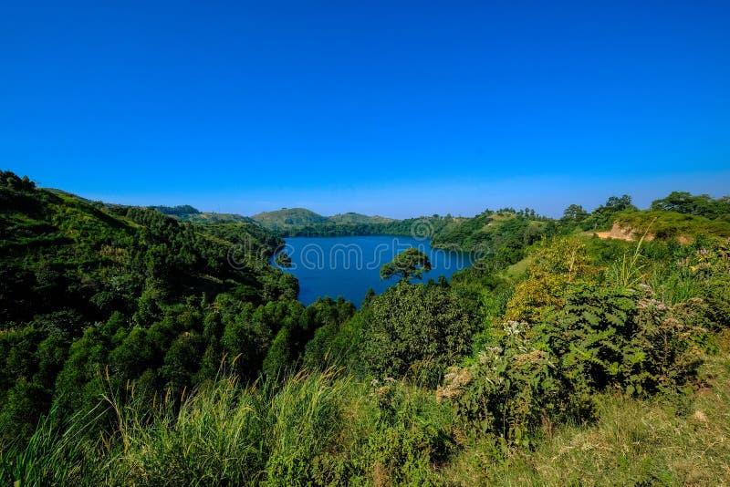 Piękny strzał rzeka otaczająca zielonymi wzgórzami z niebieskim niebem w tle zdjęcie royalty free