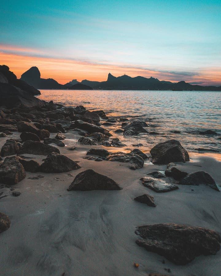 Piękny strzał skalisty wybrzeże morze przy zmierzchem z zadziwiającym niebieskim niebem obrazy stock