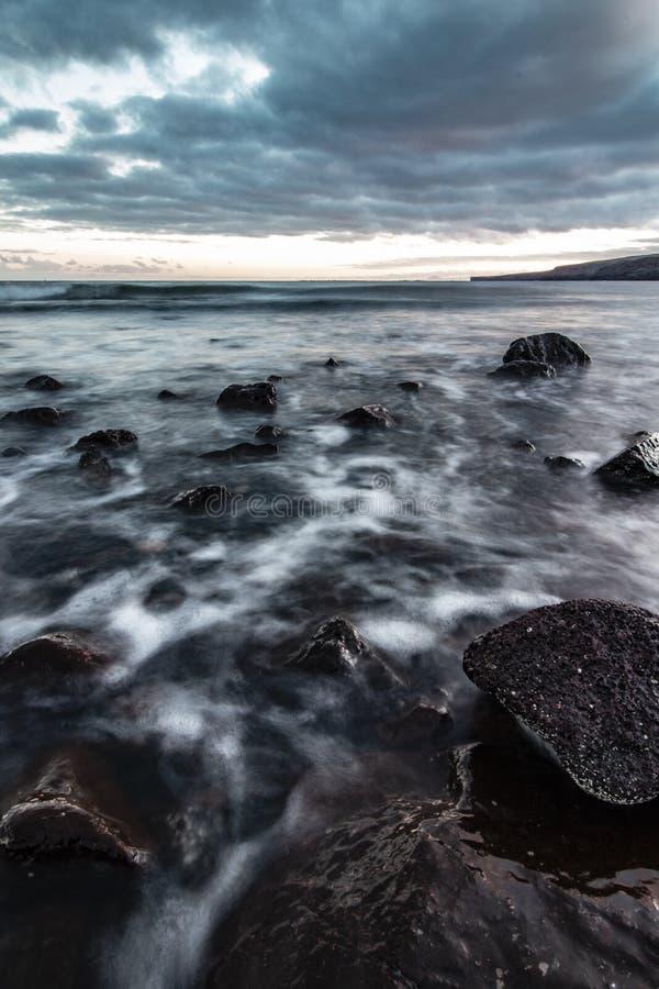 Piękny strzał skalisty wybrzeże morze z zadziwiającą wodną teksturą i breathtaking chmurnym popielatym niebem zdjęcie stock