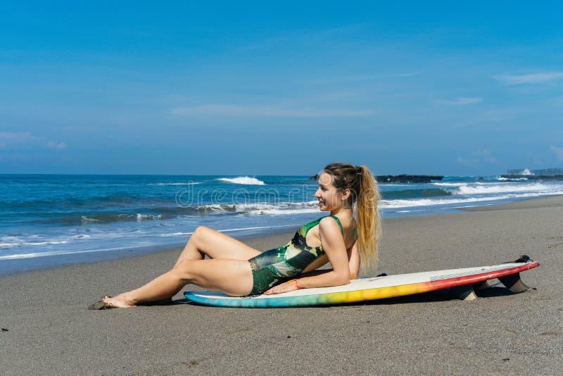 piękny surfingowiec relaksuje na plaży w swimsuit obraz royalty free