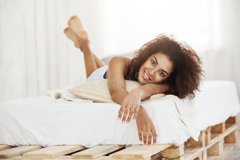 Piękny szczęśliwy afrykański dziewczyny lying on the beach na łóżku ono uśmiecha się w domu patrzejący kamerę fotografia royalty free