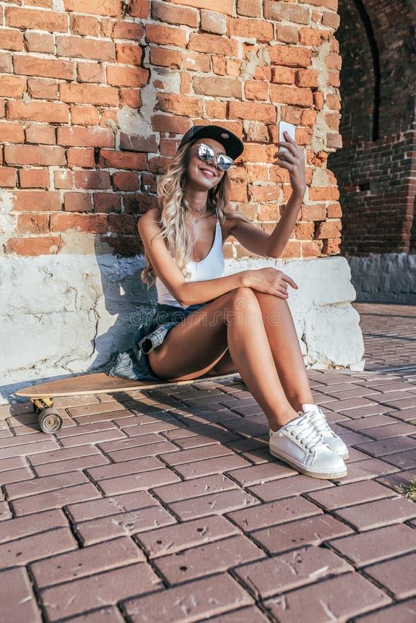 Piękny szczęśliwy dziewczyny obsiadania deskorolka, longboard On mienia smartphone jego ręka, opowiada wideo wezwanie, online obrazy stock