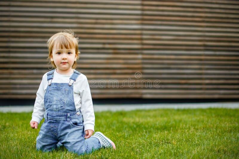 Piękny szczęśliwy mały dziewczynki obsiadanie na zielonej łące na naturze w parku obraz royalty free