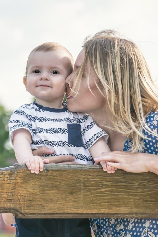 Piękny szczęśliwy mather całuje jej dziecko syna plenerowego na ławce obrazy stock
