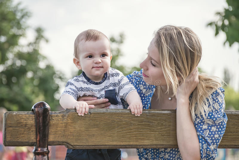 Piękny szczęśliwy mather z synem plenerowym na ławce troszkę zdjęcie royalty free
