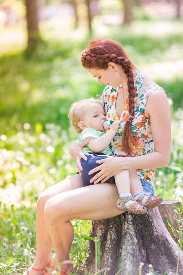 Piękny szczęśliwy matki breastfeeding plenerowy obrazy royalty free