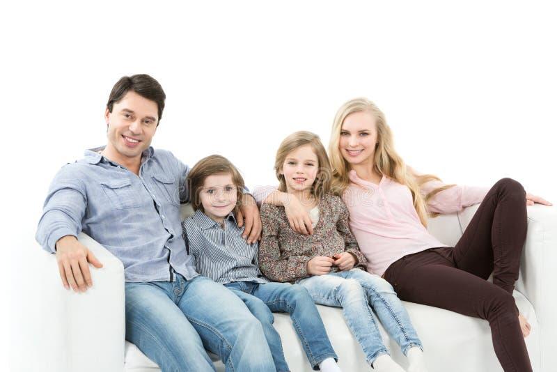 Piękny szczęśliwy rodzinny obsiadanie wpólnie fotografia stock