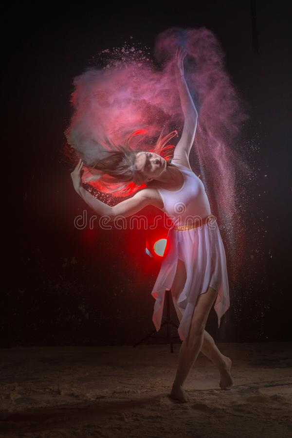 Piękny szczupły żeński tancerz w studiu podczas Prochowego sesja zdjęciowa. z barwionym światłem zdjęcie stock
