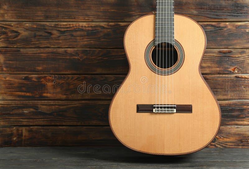 PiÄ™kny sześć - smyczkowa klasyczna gitara przeciw drewnianemu tÅ'u zdjęcia royalty free