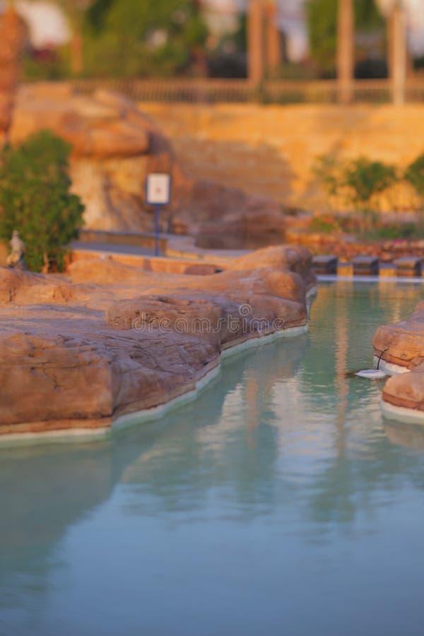 Piękny sztuczny jezioro wśród kamieni w hotelowym kompleksie przy zmierzchem w lecie obraz stock