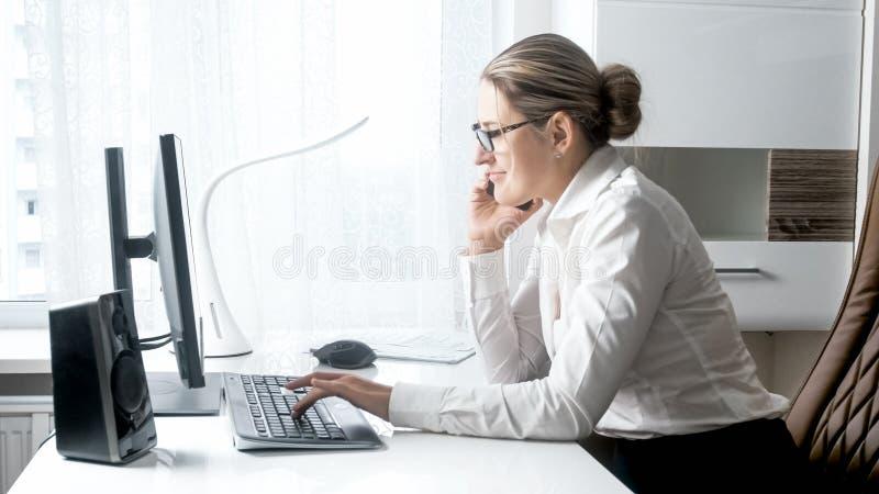 Piękny uśmiechnięty bizneswoman opowiada telefonem komórkowym w biurze zdjęcia stock