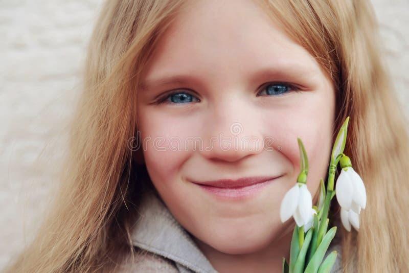 Piękny uśmiechnięty blondyn z długie włosy małą dziewczynką z bukietem pierwszy wiosna kwitnie śnieżyczki Dziewczyna trzyma kwiat zdjęcie royalty free
