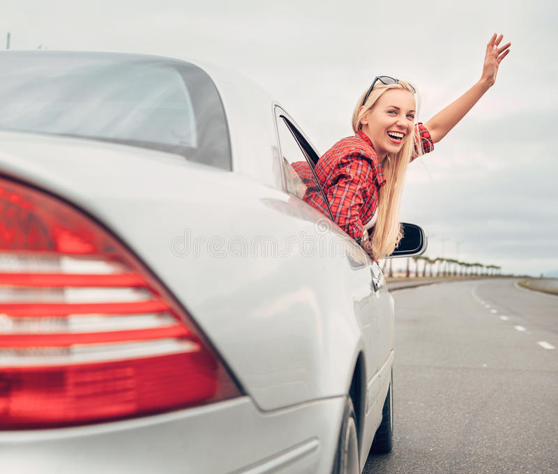 Piękny uśmiechnięty damy spojrzenie out od samochodowego okno na autostradzie fotografia royalty free