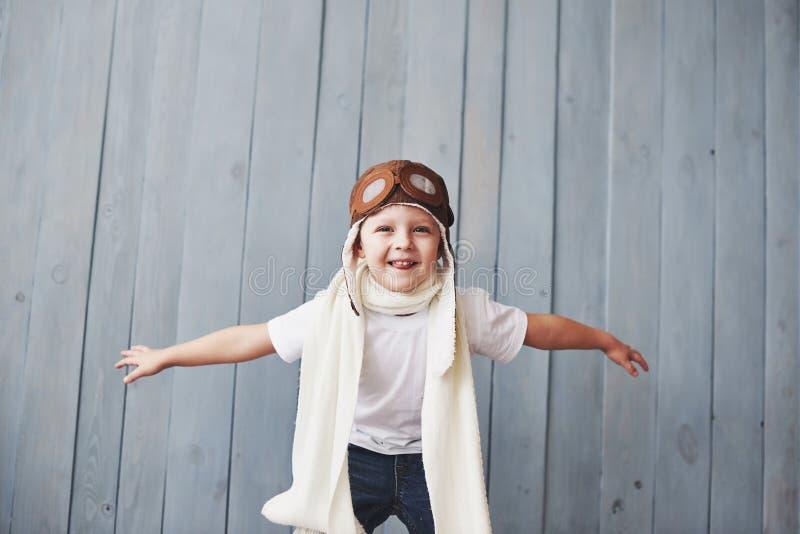 Piękny uśmiechnięty dziecko w hełmie na błękitnym tle bawić się z samolotem Rocznika pilotowy pojęcie zdjęcia stock