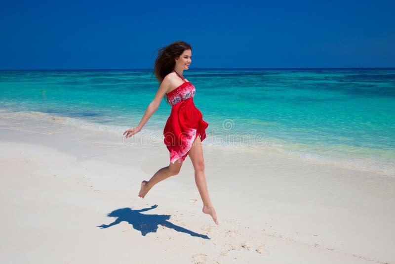 Piękny uśmiechnięty dziewczyna bieg na egzot plaży z białym piaskiem a zdjęcie royalty free