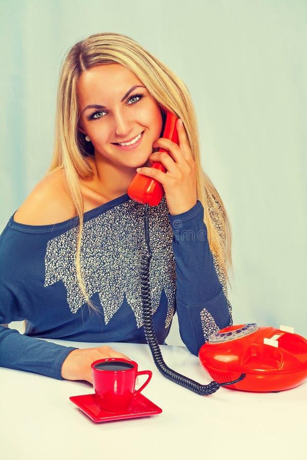 Piękny uśmiechnięty młody żeński obsiadanie blisko speaki i stołu zdjęcia royalty free