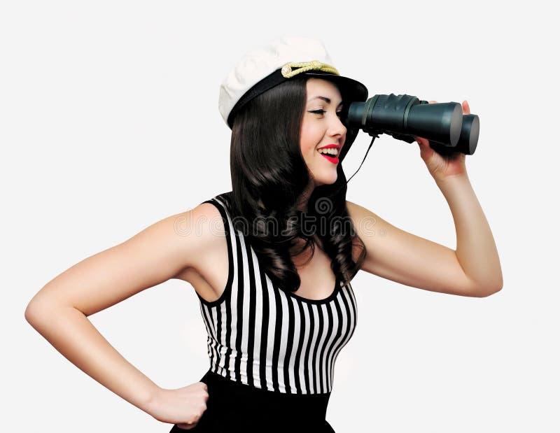 Piękny uśmiechnięty młody brunetki kobiety żeglarz patrzeje daleko od przez lornetek na bielu fotografia royalty free