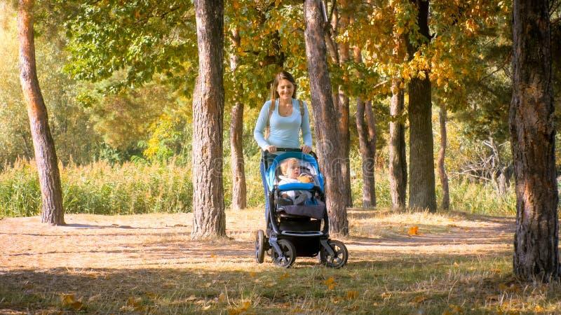 Piękny uśmiechnięty macierzysty odprowadzenie w parku z jej berbecia syna obsiadaniem w pram obrazy royalty free