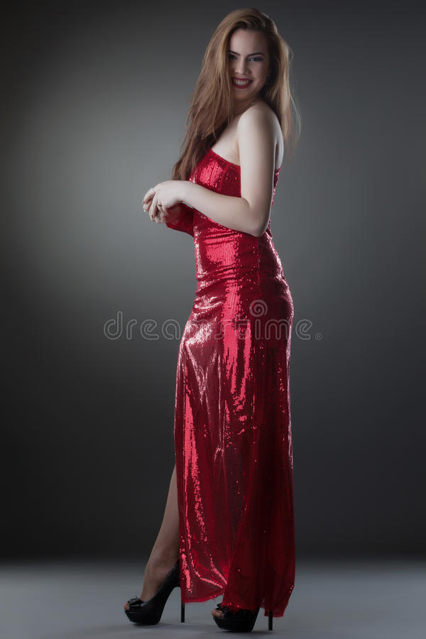 Piękny uśmiechnięty model pozuje w długiej błyszczącej sukni zdjęcia stock
