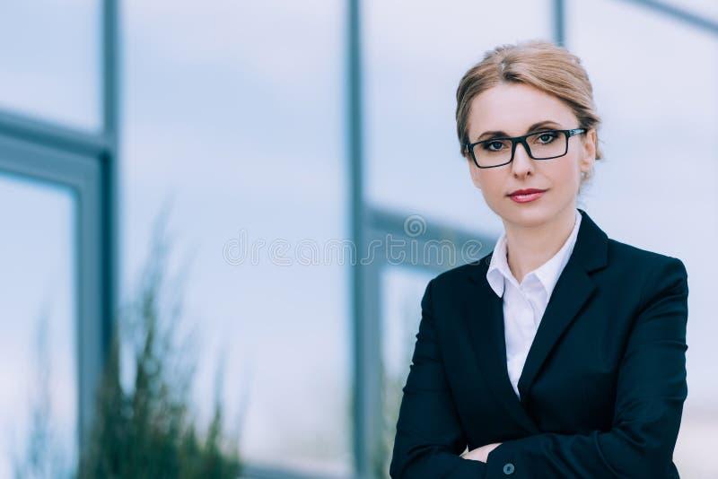 Piękny w średnim wieku bizneswoman stoi z krzyżować rękami i patrzeje kamerę w eyeglasses fotografia stock