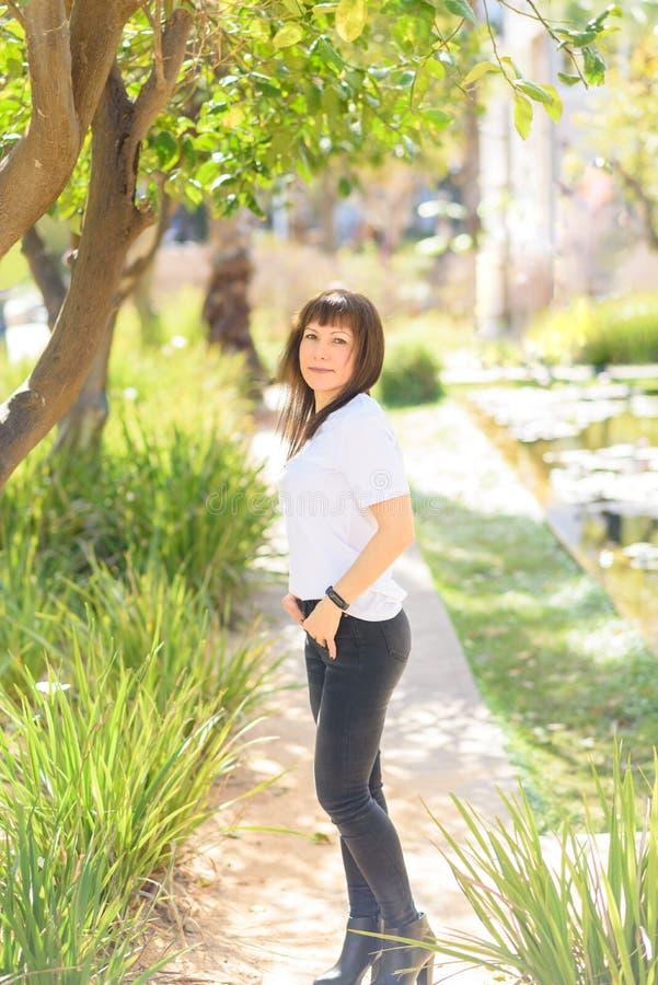 Piękny w średnim wieku kobiety ono uśmiecha się życzliwy in camera i patrzeć w pięknym natury tle fotografia stock