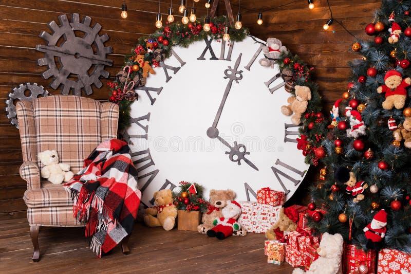 Piękny wakacje dekorował żywego pokój z choinką i teraźniejszość Duży magiczny zegar na drewnianej ścianie Zima wakacji projekt fotografia royalty free