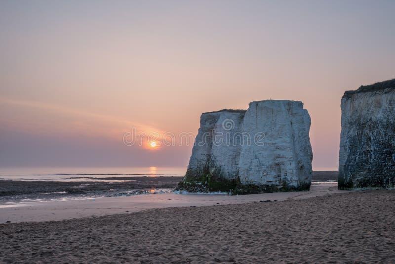 Piękny wibrujący wschód słońca nad skał stertami na plaży przy niskim przypływem obrazy royalty free