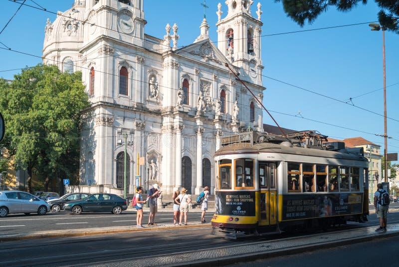 Piękny widok Estrela bazyliki fasada 28 przy tramwajową przerwą i historyczny żółty tramwaj fotografia royalty free