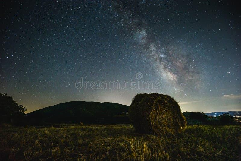 Piękny widok grający główna rolę nocne niebo z milky sposobem nad kultywującym polem z siano belą fotografia royalty free