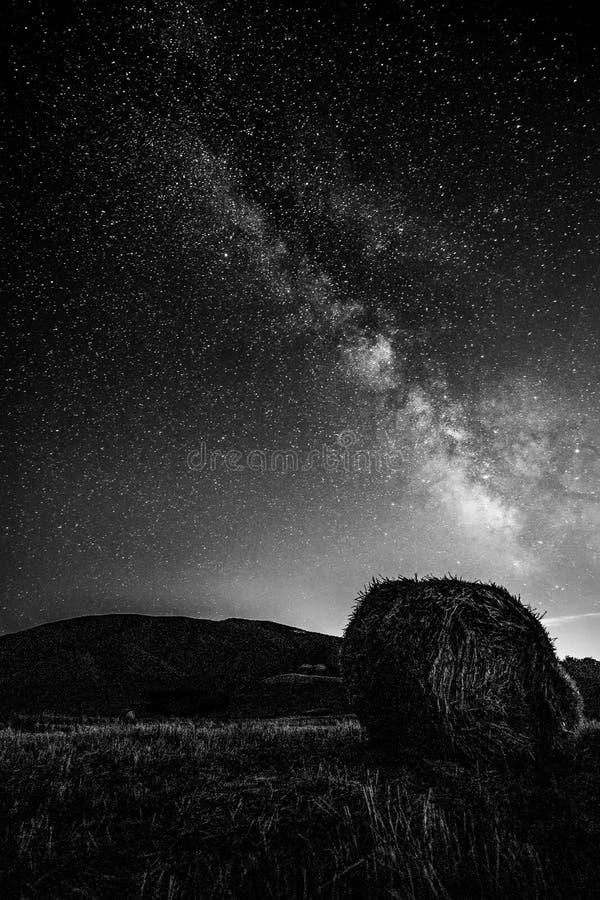 Piękny widok grający główna rolę nocne niebo z milky sposobem nad kultywującym polem z siano belą zdjęcia stock