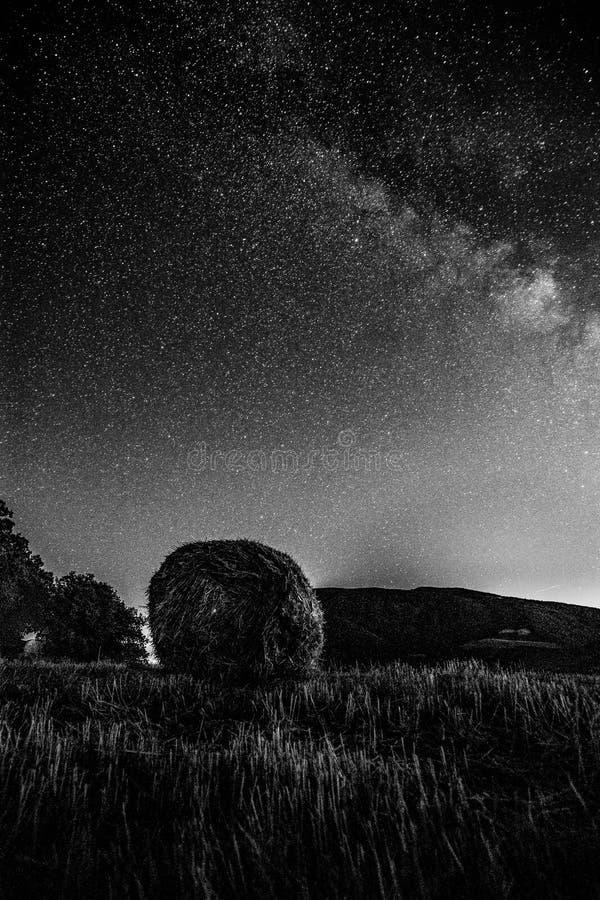 Piękny widok grający główna rolę nocne niebo z milky sposobem nad kultywującym polem z siano belą zdjęcia royalty free