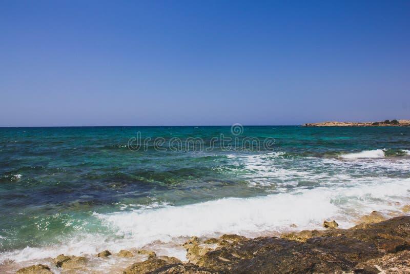 Piękny widok jasny morze śródziemnomorskie z biel piany falą na skalistym brzeg Pogodny seascape w Cypr obrazy royalty free