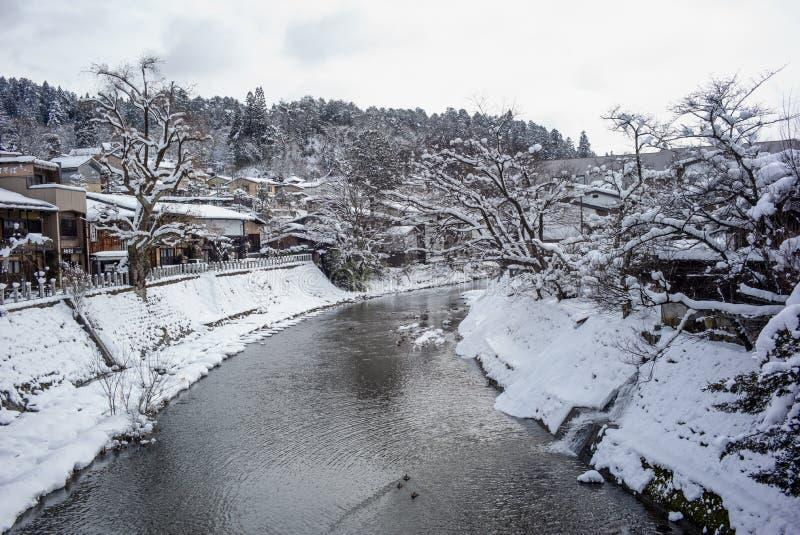 Piękny widok miyagawa rzeki pokrywa z śniegu i rocznika budynków widokiem patrzeje od czerwień mostu w Takayama widoku miejscowy zdjęcie royalty free