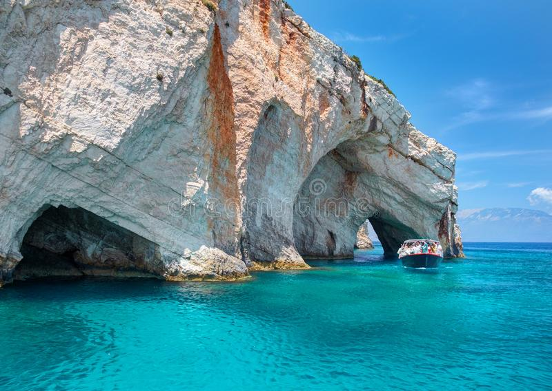 Piękny widok na rockowych arces łukach błękit jamy i podróży zwiedzająca łódź z turystami w błękitne wody Sławni Grecja wakacje obraz stock